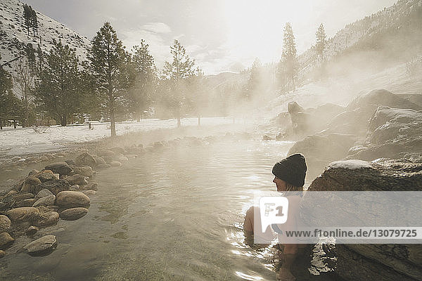 Side view of woman wearing bikini while sitting in thermal pool at forest during winter