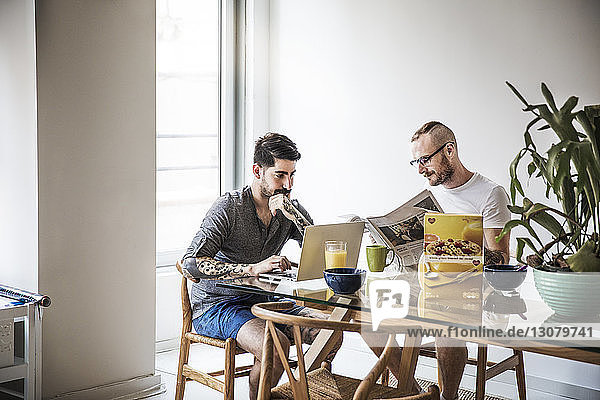 Homosexual couple using laptop and reading newspaper at breakfast table