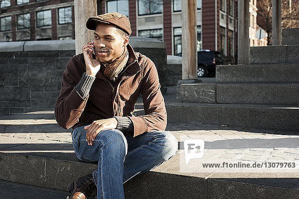 Mann benutzt ein Smartphone  während er auf einer Treppe sitzt