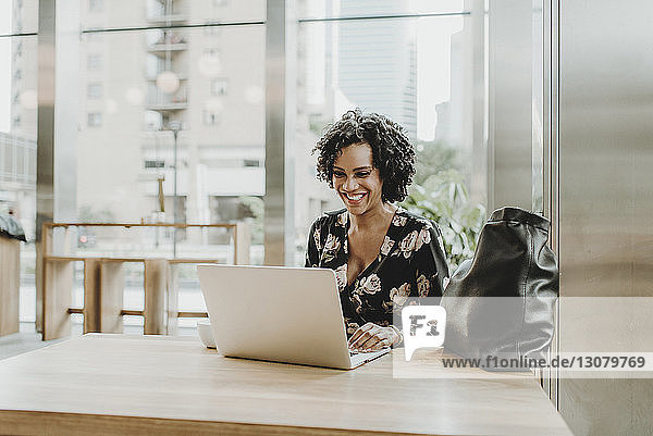 Smiling woman using laptop computer while sitting at table in cafe