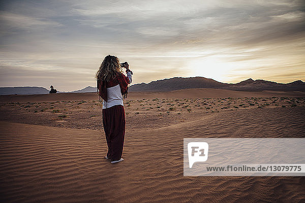 Rear view of woman photographing through mobile phone at desert against cloudy sky
