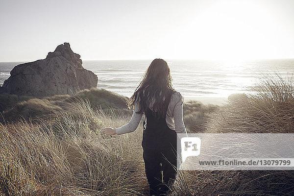 Rückansicht einer Frau  die auf einem zum Meer führenden Weg geht