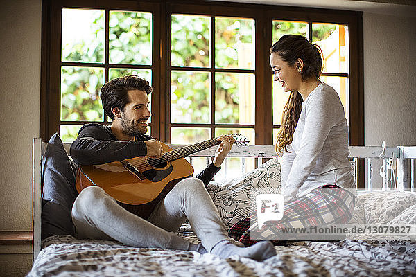 Man playing guitar to girlfriend while resting on alcove window seat at home