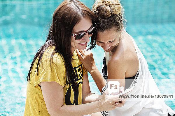 Liebevolle Freundinnen mit Smartphone am Pool