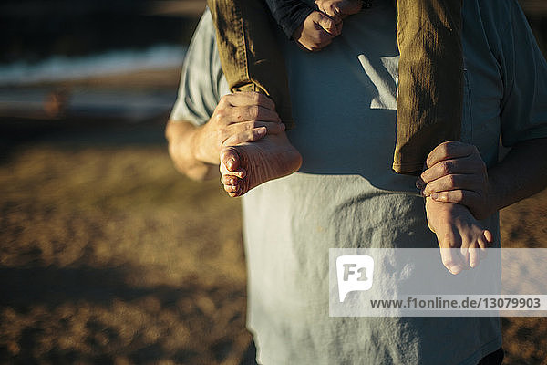 Mittelteil des Grossvaters  der den Enkel auf den Schultern auf dem Feld trägt