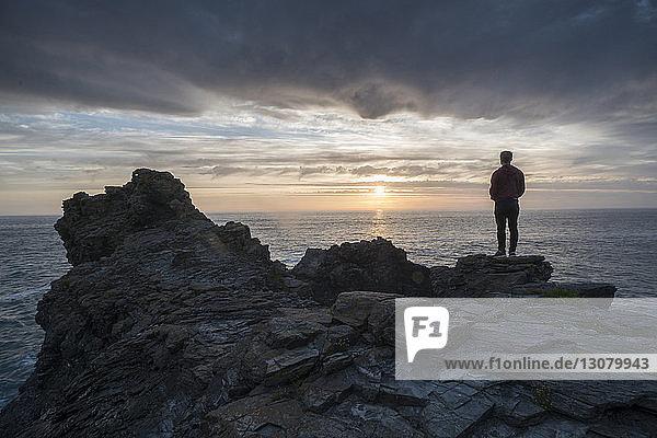 Rückansicht eines auf einer Klippe am Strand stehenden Silhouettenmannes vor bewölktem Himmel bei Sonnenuntergang