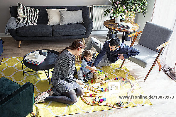 High angle view of parents looking at son playing with toy train at home
