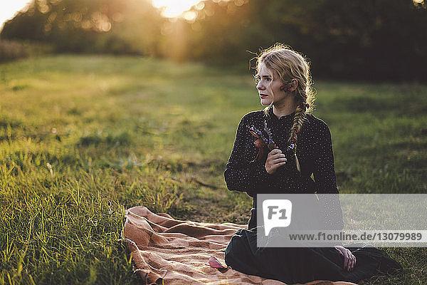 Nachdenkliche junge Frau mit geflochtenem Haar schaut weg  während sie auf einer Decke im Grasfeld sitzt