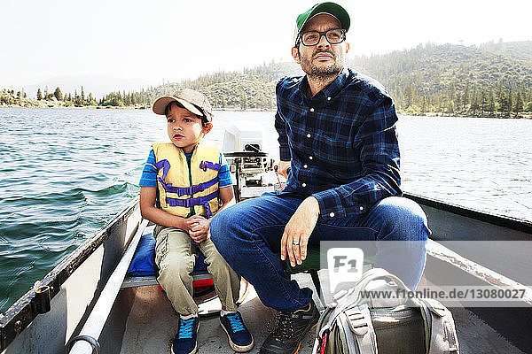 Father and son traveling in motorboat on lake
