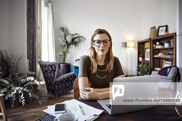 Portrait of confident businesswoman sitting at table with laptop in office