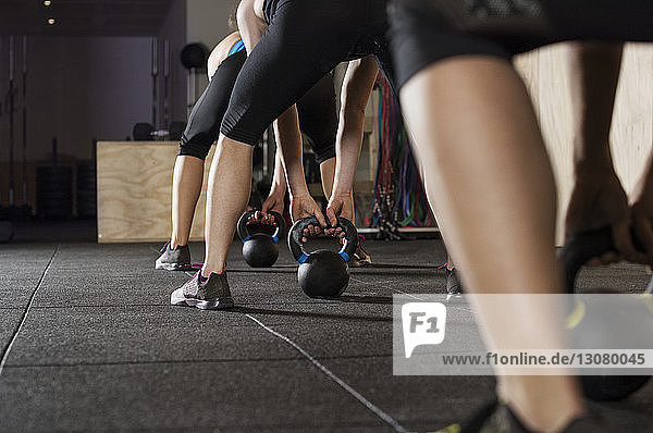Low section of female athletes exercising with kettle bells in gym