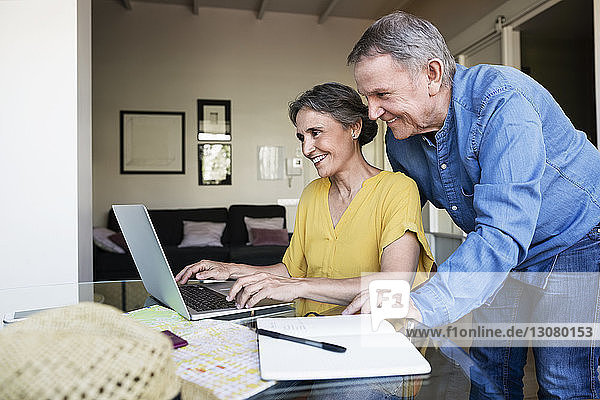 Senior couple using laptop while planning vacation at home