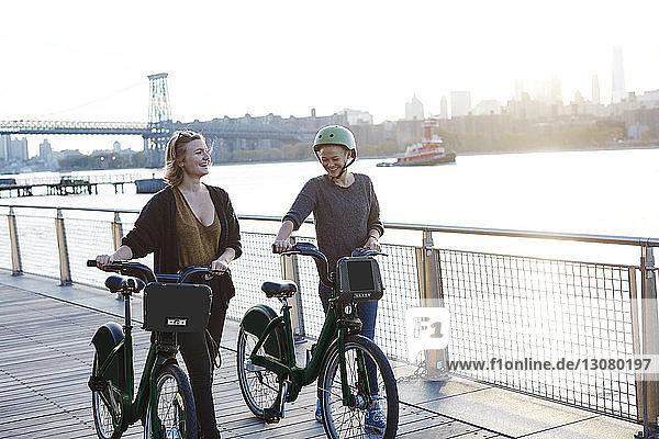 Lächelnde Freunde mit Fahrrädern auf der Promenade am Fluss