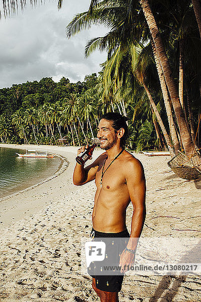 Cheerful shirtless man having drink while standing at beach