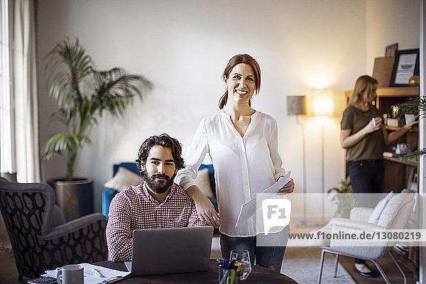 Porträt einer glücklichen Geschäftsfrau mit einem männlichen Kollegen am Tisch im Kreativbüro