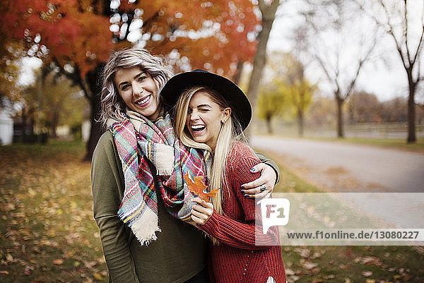 Lächelnde weibliche Unholde stehen im Herbst auf dem Feld