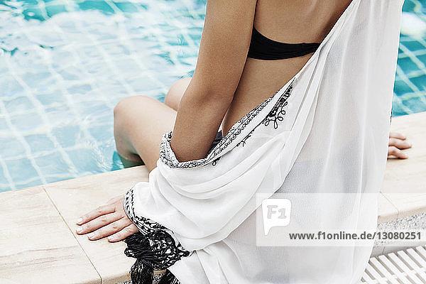 Mittendrin sitzende Frau am Pool