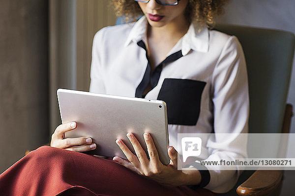 Mittelsektion einer Geschäftsfrau  die einen Tablet-Computer in der Hotellobby benutzt