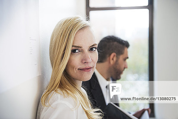 Portrait of businesswoman standing by colleague in office