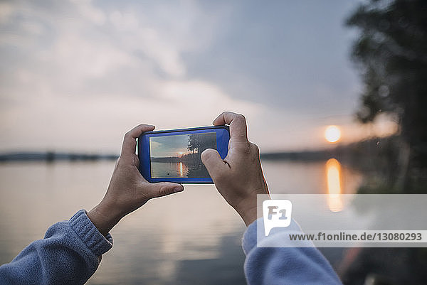 Abgetrennte Hände eines Touristen  der im Yellowstone-Nationalpark bei Sonnenuntergang mit einem Smartphone einen See fotografiert