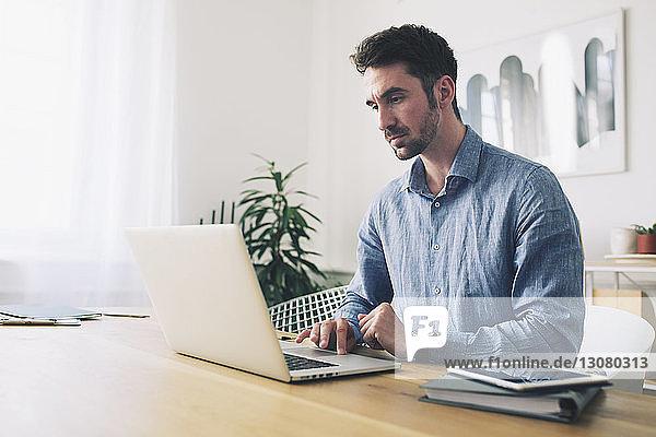 Geschäftsmann mit Laptop-Computer am Schreibtisch im Büro