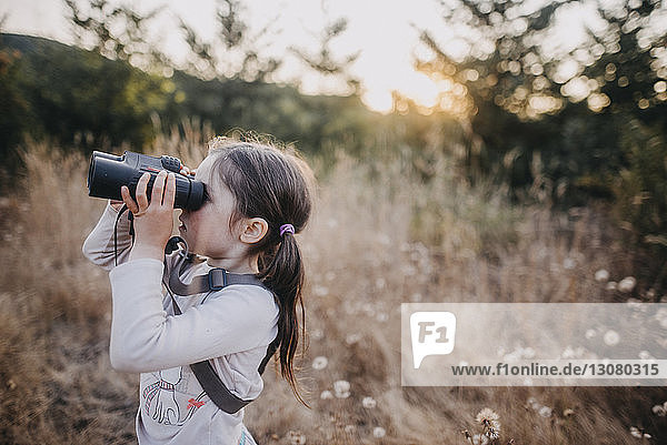 Side view of girl looking through binoculars while standing on field