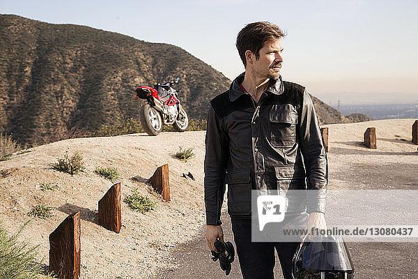 Nachdenklicher Motorradfahrer  der einen Helm hält  während er auf einem Berg steht