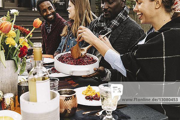 Glückliche Freunde unterhalten sich beim Essen am Tisch