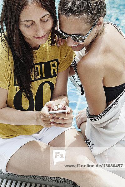 Hochwinkelansicht von Freundinnen mit Smartphone am Pool