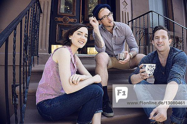 Porträt einer Frau mit männlichen Freunden auf einer Treppe vor dem Haus sitzend