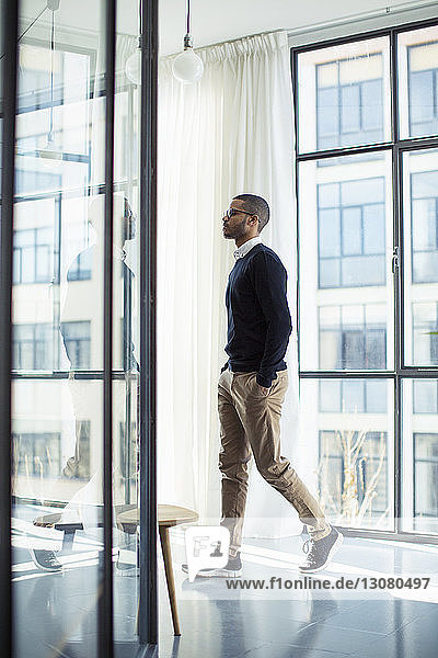 Side view of businessman with hands in pockets walking at office corridor