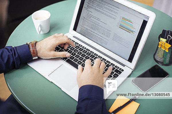 Abgetrennte Hände eines Geschäftsmannes  der am Laptop arbeitet