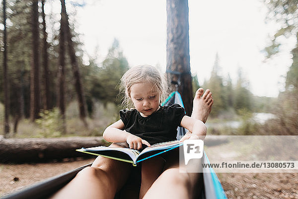 Cropped legs of mother around daughter reading story book in hammock at campsite