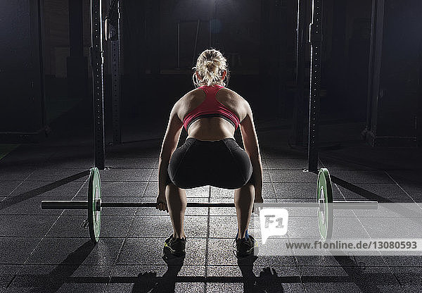 Rear view of woman picking barbell at gym