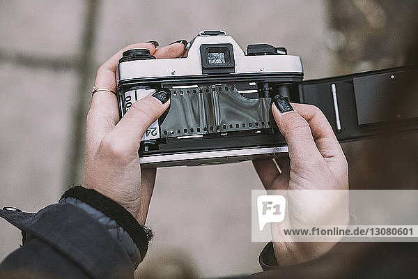 Close-up of woman loading film negative in vintage camera on footpath