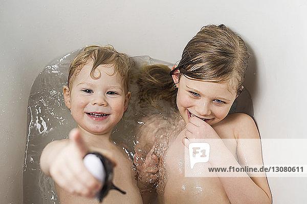 Porträt eines glücklichen Bruders mit einer Schwester  die zu Hause in der Badewanne badet