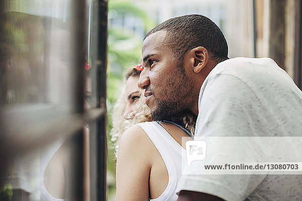 Close-up of thoughtful couple looking through window while standing at home
