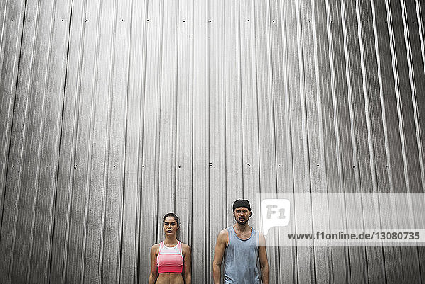 Low angle view of couple standing against metallic wall