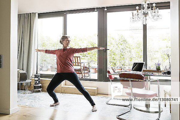 Mature woman practicing yoga in Warrior 2 pose at home