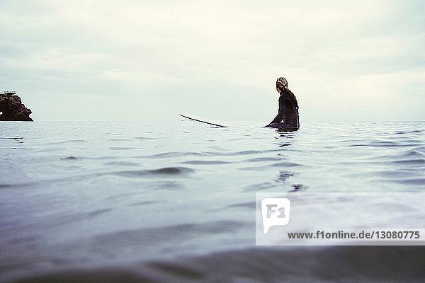 Seitenansicht einer Frau  die auf einem Surfbrett im Meer vor bewölktem Himmel sitzt