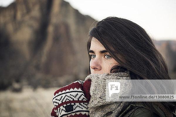 Nahaufnahme einer Frau  die weg schaut  während sie im Smith Rock State Park am Berg steht