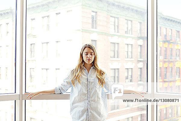 Frau mit geschlossenen Augen steht am Fenster in der Stadt