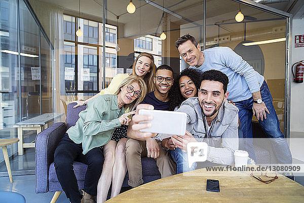 Happy business people talking selfie in office
