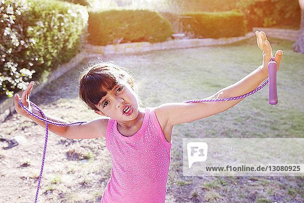 Porträt eines Mädchens  das mit ausgestreckten Armen ein Springseil auf dem Feld hält