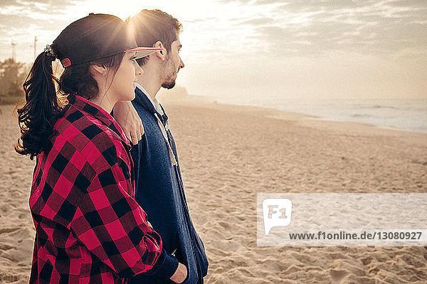 Junges Paar betrachtet Sonnenuntergang am Strand