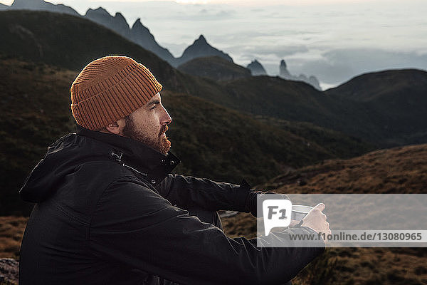 Thoughtful man holding mug while sitting on mountain