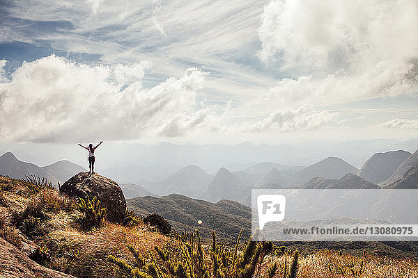Distant view of female hiker standing with arms outstretched on mountain against cloudy sky