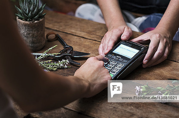 Cropped image of customer paying with credit card in flower shop