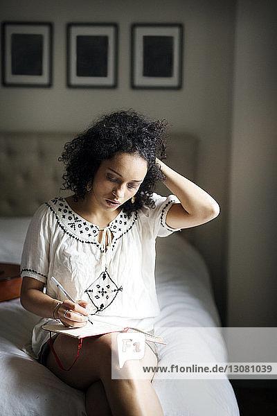 Frau mit Hand im Haar schreibt auf Buch
