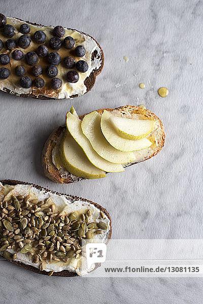 Hochwinkelansicht von gerösteten Broten mit Kürbiskernen und Früchten auf dem Tisch